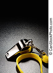Whistle - Metal whistle on a black grained surface