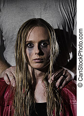 abused woman with man standing behi - portrait of an abused...