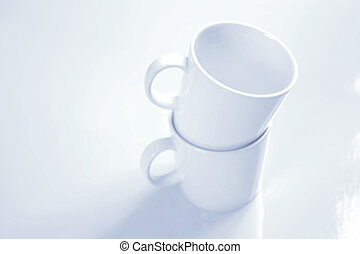 Two Mugs - Two white porcelain mugs stacked on top of each...