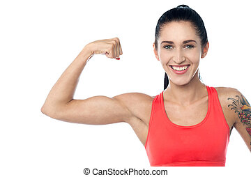 Fitness trainer flexing her biceps - Smiling young fit gym...