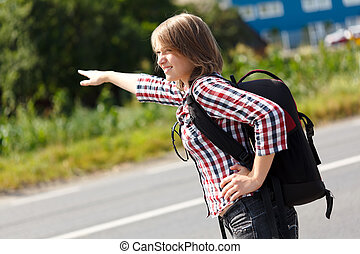 Teen girl hitch hiking on the road