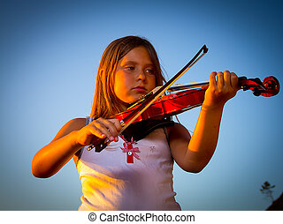 little girl playing violin on the beach