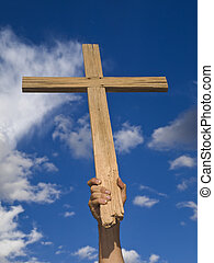 Keeping the faith - A mans hand keeping a wooden cross high...