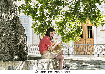 girl with straw hat in here hands sitting under a tree