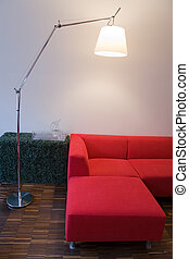 Living room interior with wooden floor, red sofa and...