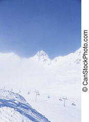 Chairlift in mountains and panoramic view on winter alps...