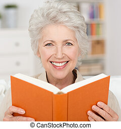 Attractive senior woman reading a book - Attractive grey...