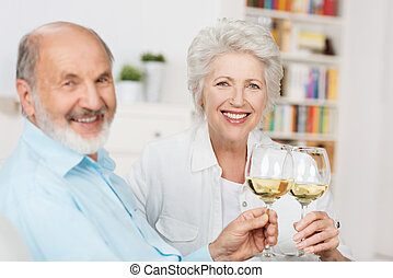 Happy senior couple toasting each other - Happy senior...