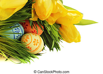 Easter eggs in grass with tulips