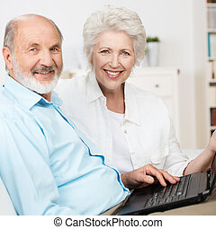 Elderly couple using a laptop computer as they sit side by...