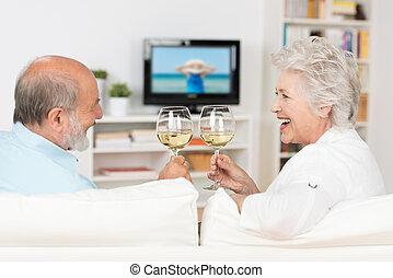 Senior couple celebrating with white wine clinking their...
