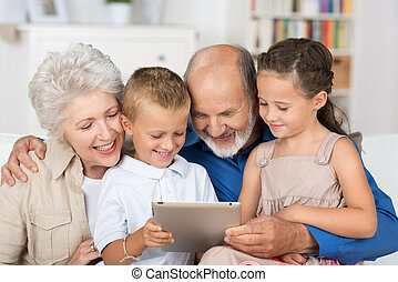 Cute boy and girl looking at a PC tablet - Cute boy and girl...