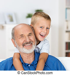 Laughing grandfather with his grandson as they play together...