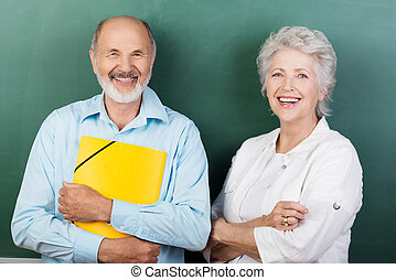 Confident happy senior couple standing with folded arms...
