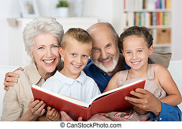 Elderly couple reading to their grandchildren as they all...
