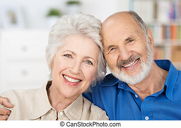 Affectionate happy retired couple with their heads together...