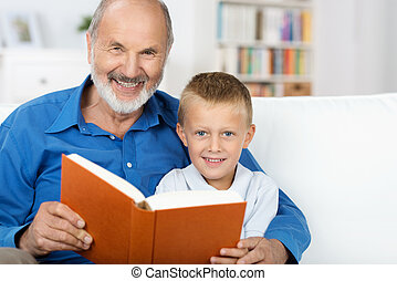Grandad and grandson enjoying a book together - Elderly...