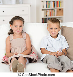 Little brother and sister sitting on a couch - Adorable...