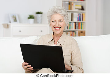 Senior woman working an a laptop balanced on her lap as she...