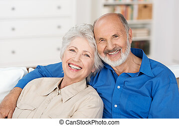 Romantic senior couple sitting close together on a sofa in...