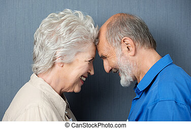 Playful loving senior couple standing facing each other with...