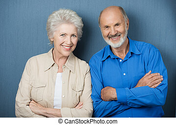 Confident elderly couple with folded arms standing side by...