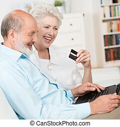 Senior couple buying online sitting together on a sofa with...