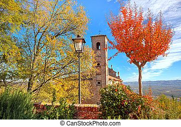 Old belfry among autumnal trees in Piedmont, Italy. - Old...
