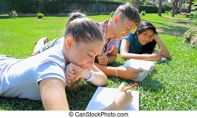 Three students in park thumb up - Young boy and two girls...
