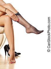 putting on stockings - woman putting on nylon stockings