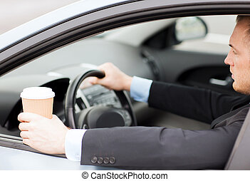 man drinking coffee while driving the car - transportation...