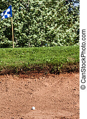 Sand trap - White golf ball on the edge of a sand hazard