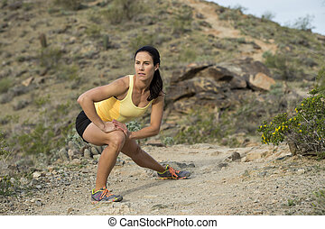 Desert Trail Stretch - Young woman stretching to warm up for...