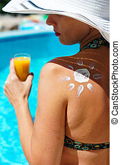 Woman in a pool - A sun made with suncream at the shoulder