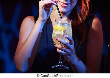 Cocktail party - Young woman holding a cocktail glass, hands...