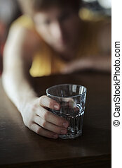 Alcohol addiction concept - Drunk boy on a bar table holding...