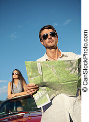 Travel destination - Handsome man holding a roadmap and...