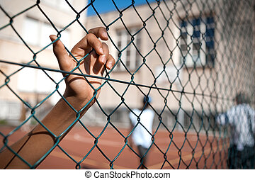 hand - A boy's hand clinging on to a fence, basketball court...