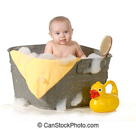 baby bathtime - cute baby in a basin with soap suds