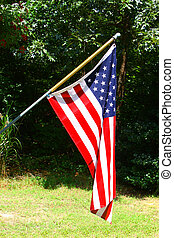 An American Stars and Stripes flag flying outside on a summer day representing freedom, patriotism and honor