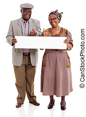 elderly african couple holding blank banner - cheerful...