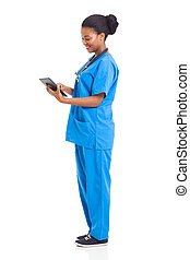side view of african american nurse using tablet computer -...