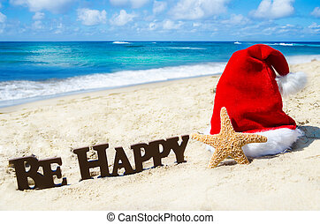 """Sign """"Be Happy"""" and starfish with christmas hat on the sandy beach by the ocean in sunny day"""