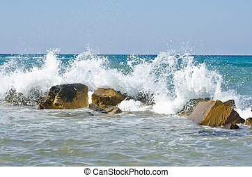 waves hitting stones near a beach