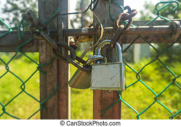 Old padlock and rusty chain at fence