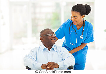 african nurse taking care of senior patient in wheelchair -...