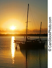 Dawn Over Water - Daybreak through clouds over an old ketch.