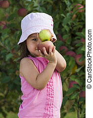 Girl posing with apples - Child posing with 2 apples stacked...