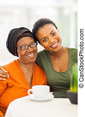 senior african woman with daughter at home - happy senior...