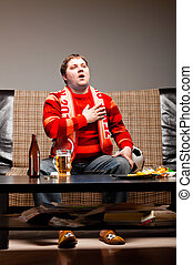 soccer fan on sofa - soccer supporter is sitting on sofa in...